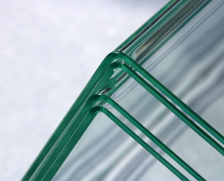 Using the new laser-based glass-bending process, it is possible to achieve precisely defined and extremely small bend radii, so that even laminated safety glass can be bent around a corner. The sheets of glass in the image are three millimeters thick.