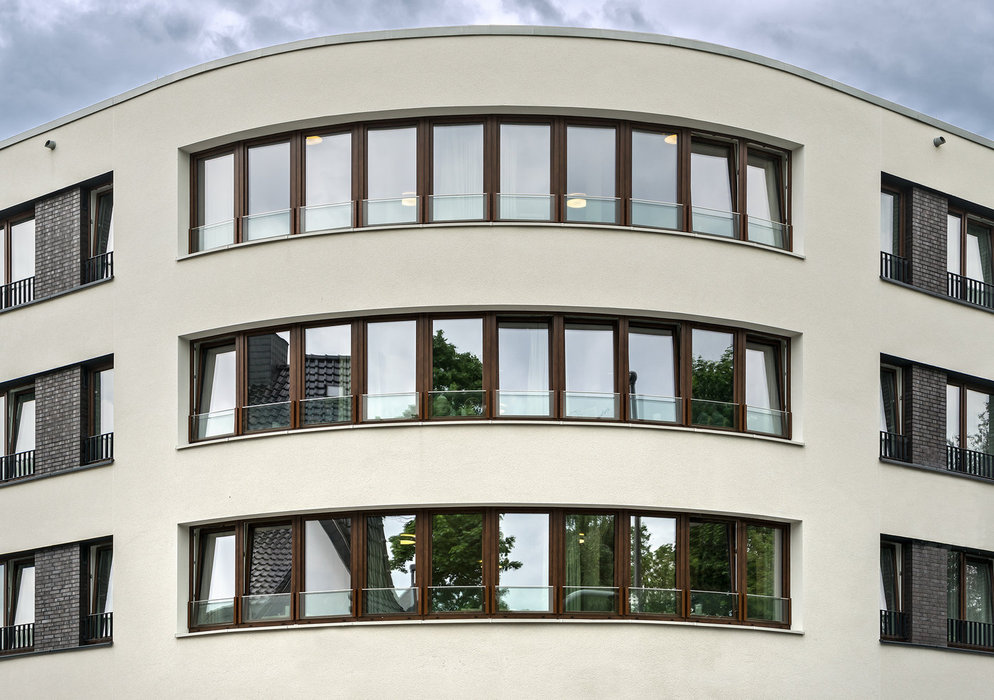 Large PVC-U system windows from the Schüco Corona CT 70 series with timber-look exterior foiling provide improved sound reduction, thermal insulation and solar shading in combination with triple insulating glass.